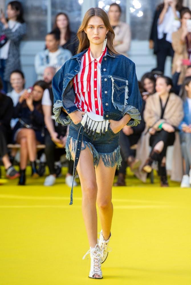 короткая синяя джинсовая куртка для девушки с карманом на груди, декорированном бахромой и вышивкой