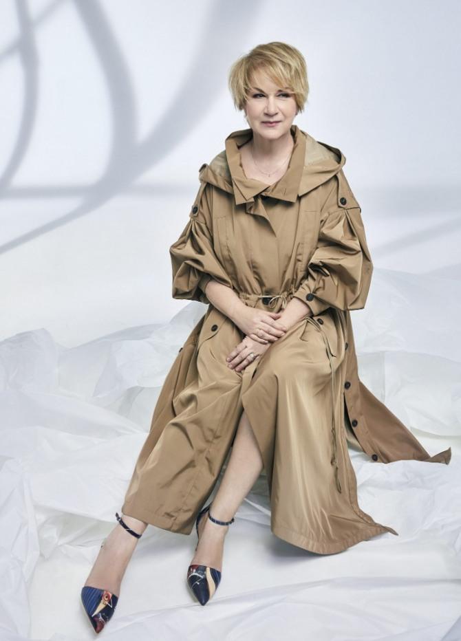 пожилая женщина в светло-коричневом стильном плаще