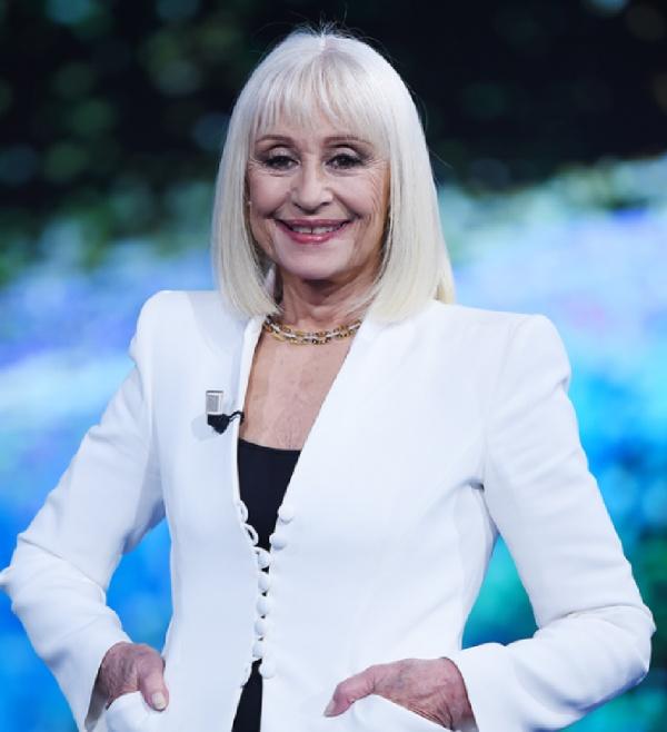 стильная стрижка женщины 75 лет с седыми волосами в комплекте с белым пиджаком