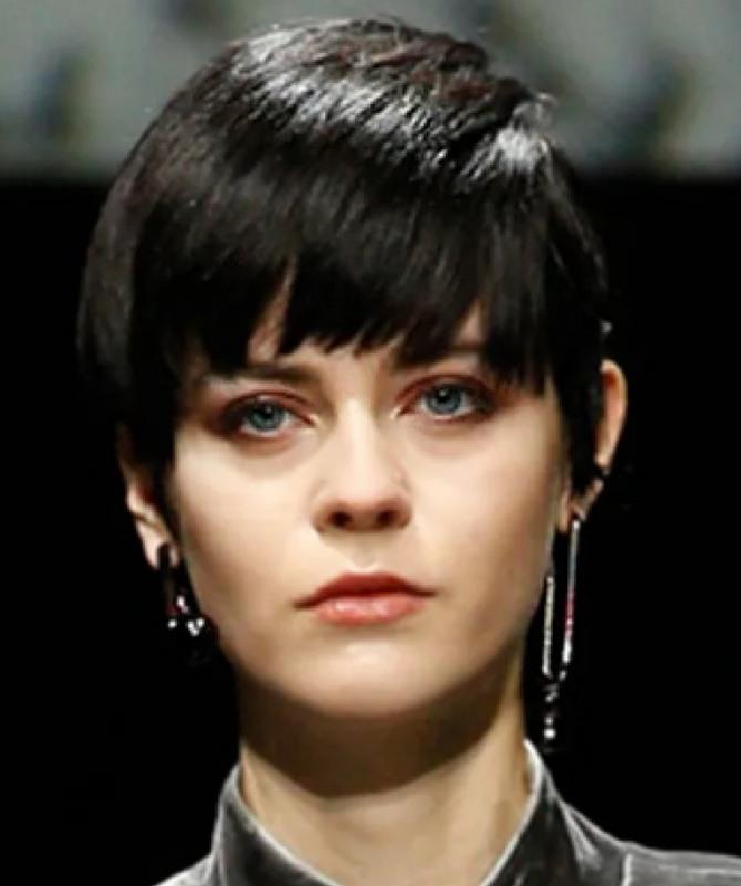 пикси на темных густых волосах - модель имеет густую рваную челку до бровей, зачесанную вперед от самой макушки