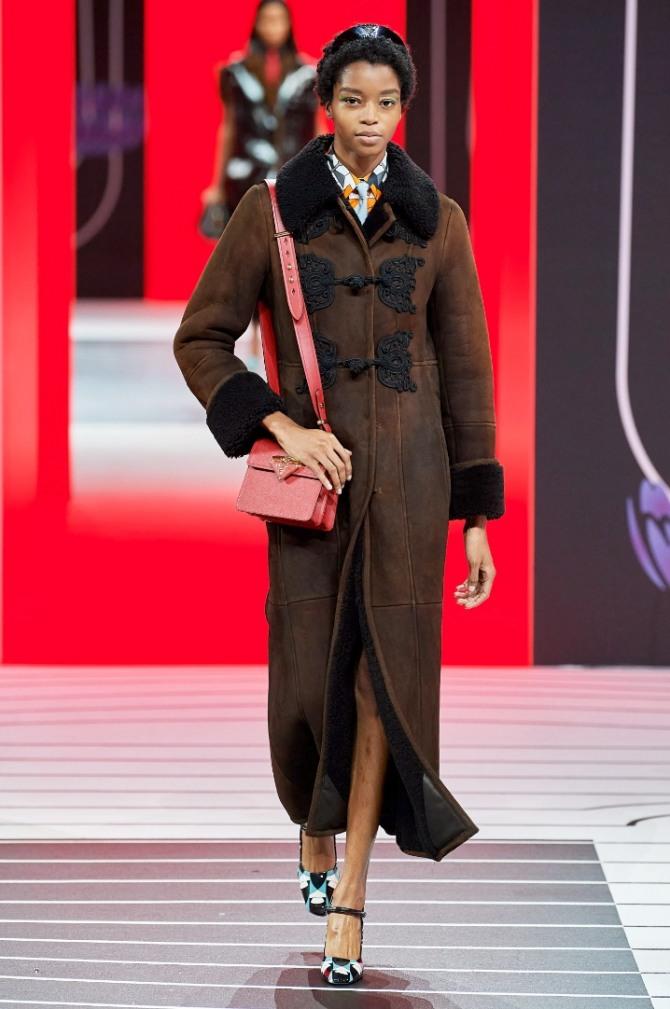Зимняя одежда из овчины. Модная дубленка 2021 года от Prada - темно-коричневая с черным воротником и черными передними аппликациями-застежками, с манжетами из черного меха на рукавах.