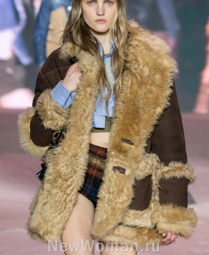 Женская одежда из дубленой овчины. фото модной дубленки 2021 года темно-коричневого цвета со светлым мехом с изнаночной стороны, на рукавах и карманах