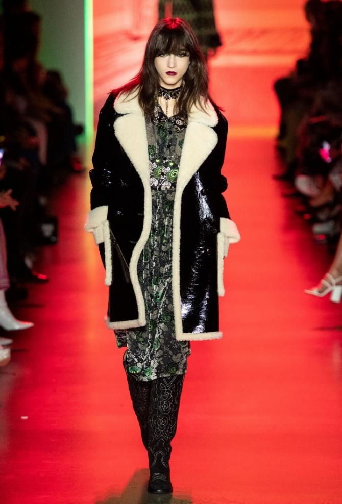 черная дубленка с блестящей пропиткой длиною выше колена со светлым мехом на воротнике и манжетах - фото модели с показа на 2021 год от бренда Anna Sui
