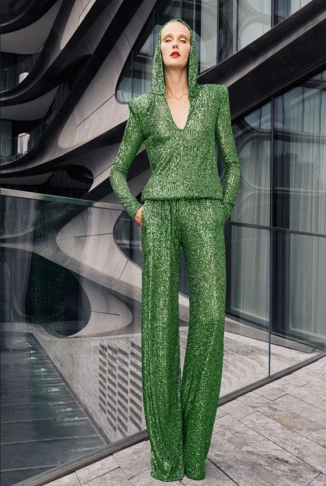 роскошный брючный вечерний женский костюм зеленого цвета из блестящей пайеточной ткани, блуза - с капюшоном